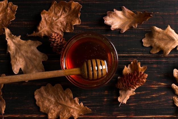 ハチミツは棒から瓶に流れ込みます。素朴な甘い秋の写真、木製の背景、乾燥した葉、copyspace。