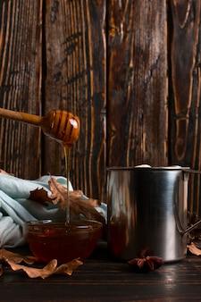 ココア、蜂蜜、マシュマロ、スパイス、木製のテーブルの乾燥した葉、スカーフの背景に鉄のマグカップ。秋の気分、温かい飲み物。 copyspace。