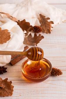 ハチミツ、スティック、ジャー、スカーフ、乾燥した葉。素朴な甘い秋の写真、白い木製の背景、copyspace。