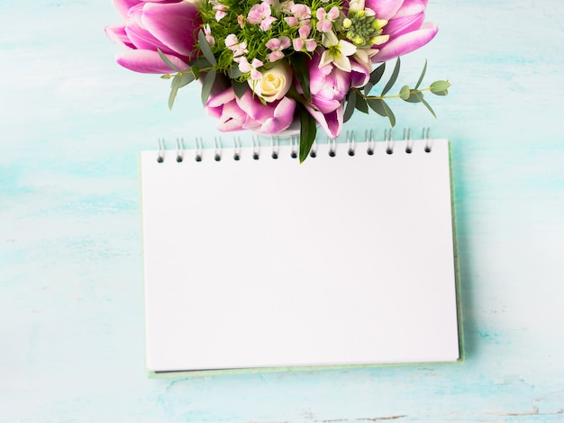 Пустая тетрадь белая страница с фиолетовыми розовыми цветами. фоновое copyspace