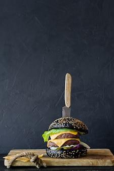 木製のまな板に黒バーガー。 copyspaceの背景