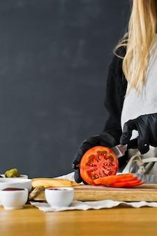 シェフは赤いトマトを切る。黒バーガーを調理するという概念。 copyspace