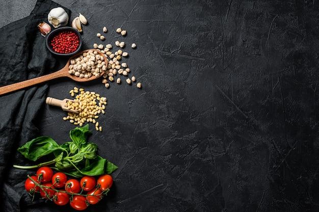フムスの材料、ニンニク、ヒヨコ豆、松の実、バジル、コショウ。上面図。 copyspaceの背景