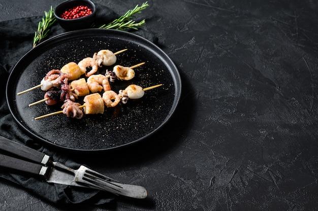 Барбекю с морепродуктами. шашлык на деревянных шпажках с креветками, осьминогом, кальмарами и мидиями. вид сверху. copyspace