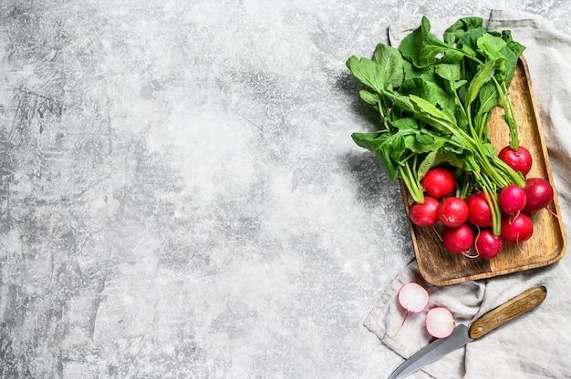 Свежие красные редиски в деревянной миске. ферма органических овощей. вид сверху. copyspace фон