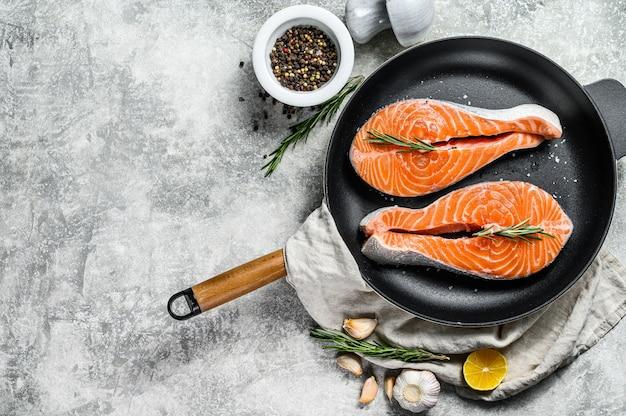 Сырой стейк из лосося в сковороде. здоровые морепродукты. вид сверху. copyspace