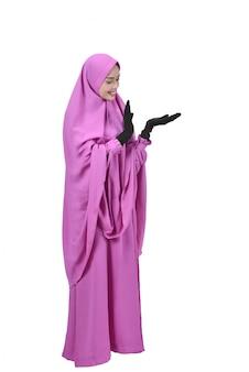 かなりアジアのイスラム教徒の女性copyspaceのための空の手を示す