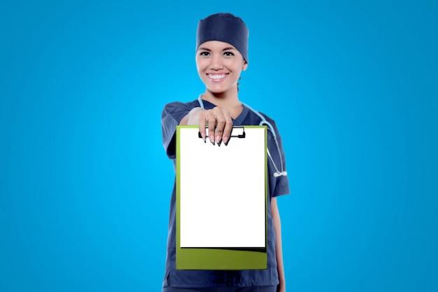 Copyspaceのための彼女の空のクリップボードを示す若いアジア女性医師