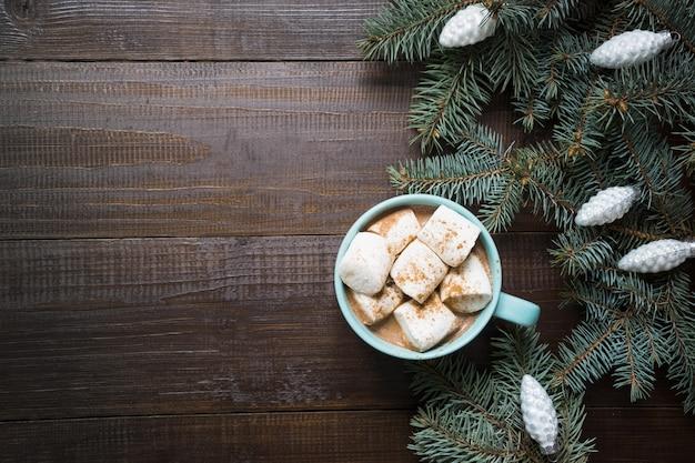 Рождественская кружка кофе с зефиром на темной деревянной доске. новый год. вид сверху и copyspace.