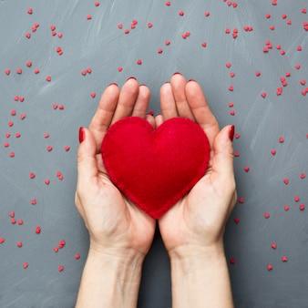 灰色の手で甘い赤いハートのバレンタインカード。 copyspace。上からの眺め。