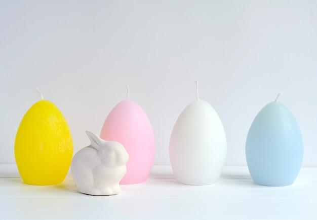 Copyspaceと白の卵形のキャンドルでイースターのウサギ