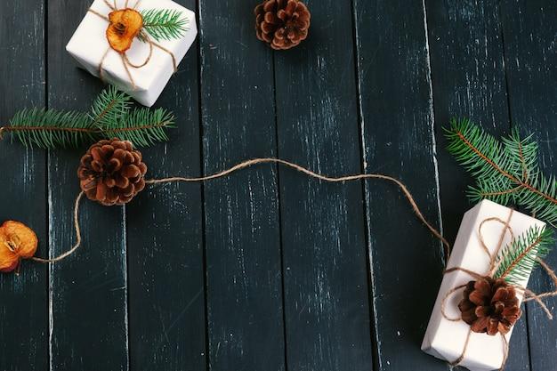 クリスマスの組成クリスマスプレゼント、ニット毛布、マツ円錐形、copyspaceと木製の背景にモミの枝