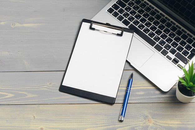 Copyspaceと木製のテーブルの供給のための空白の紙を使用してクリップボード