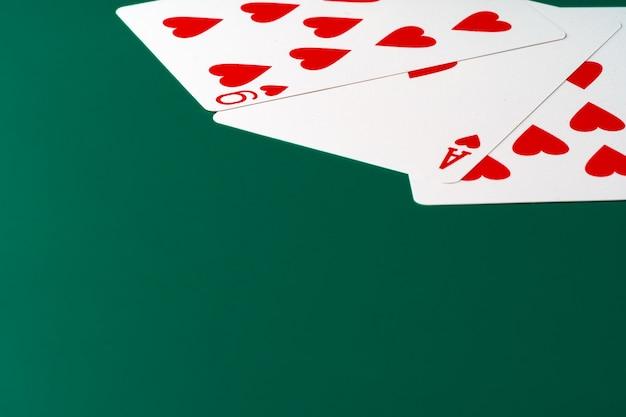 Игральные карты на зеленом столе крупным планом, copyspace