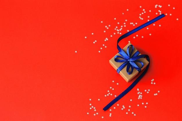 Вид сверху на рождественские подарки с лентой на фоне красной бумаги с серебряными звездами. copyspace.