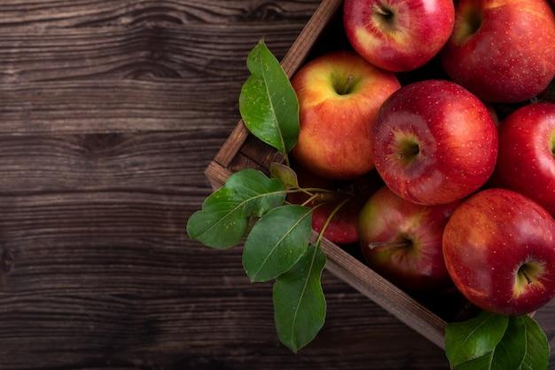 Спелые яблоки с листьями в деревянную корзину на деревенском столе. вид сверху. copyspace.