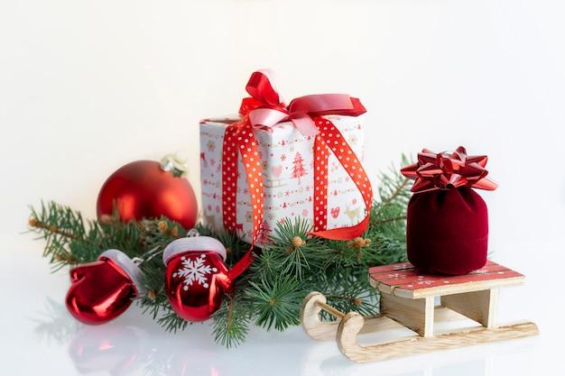 クリスマスの装飾、つまらないもの、ギフトボックス、ガントレット、白のサンタクロースのそりと組成。 copyspaceのクリスマス休暇。
