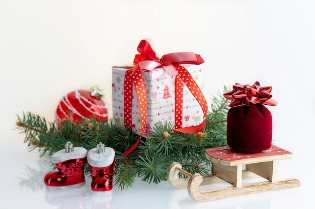 装飾、ギフトボックス、つまらないもの、ブーツ、サンタクロースのそりのクリスマス組成。白に。 copyspaceのクリスマス休暇。