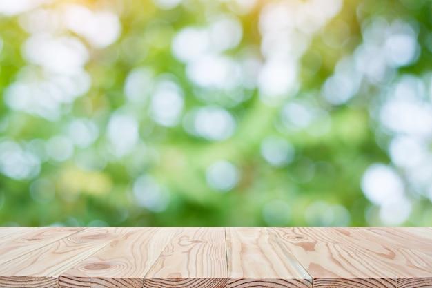空の木製テーブルトップと表示のためのcopyspaceで自然の背景をぼかしたり、あなたの製品をモンタージュ