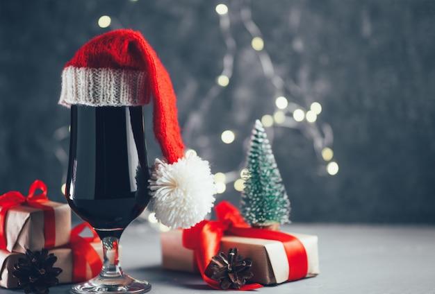 Стакан темного крафтового пива крепкий, носильщик в новогодней шапке на праздничном столе copyspace