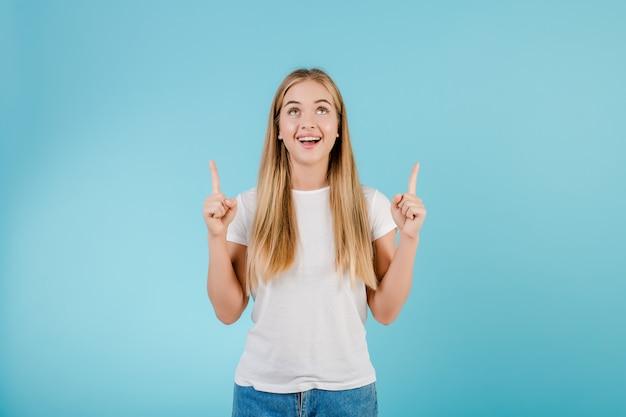 青で分離されたcopyspaceで指を指している肯定的な笑顔金髪少女