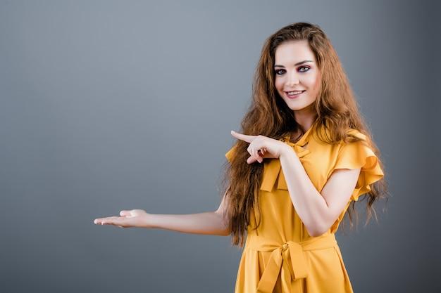 Хорошенькая молодая девушка, указывая на copyspace, изолированных на серый