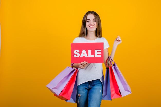 カラフルなショッピングバッグと黄色で分離されたcopyspaceテキスト販売サインバナーと美しいブルネットの女性