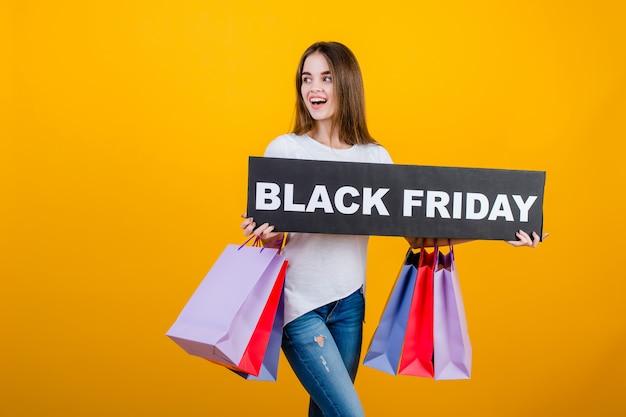 カラフルなショッピングバッグとcopyspaceテキスト黒金曜日記号バナー黄色で分離された美しいブルネットの女性