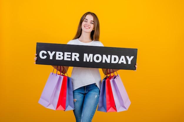 カラフルなショッピングバッグと黄色の上分離されたcopyspaceテキストサイバー月曜日記号バナーと美しいブルネットの女性