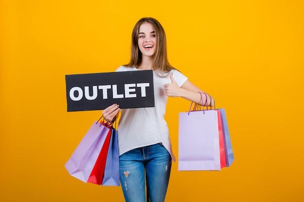 カラフルなショッピングバッグと黄色で分離されたcopyspaceテキストアウトレット記号バナーと美しいブルネットの女性