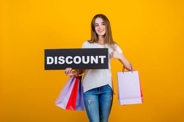 カラフルなショッピングバッグと黄色で分離されたcopyspaceテキスト割引記号バナーと美しいブルネットの女性