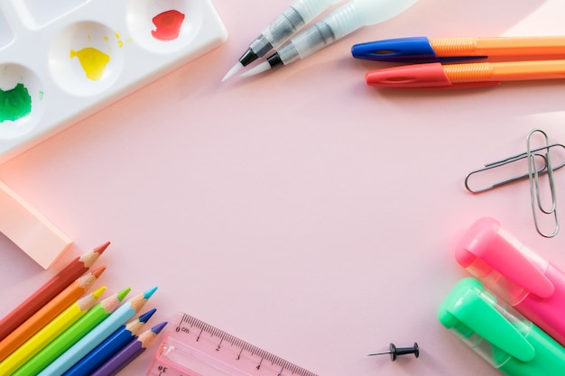Школьные принадлежности на розовом фоне. copyspace для текста
