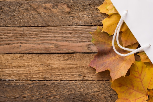 木製、copyspaceの秋の黄色の乾燥葉と白いパッケージ。秋のセール