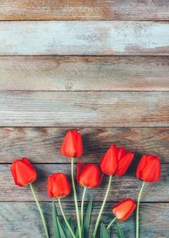 Copyspaceと水色の木製レトログランジに赤いチューリップの花束。