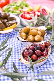 伝統的な前菜、ギリシャ料理の緑と赤のオリーブ。オリーブの新鮮な枝。 copyspace。上。青い市松模様のテーブルクロス
