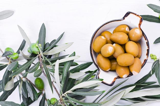 白い木製の背景に果実と新鮮なオリーブの枝。イタリアの伝統的な植物。 copyspace。平置き