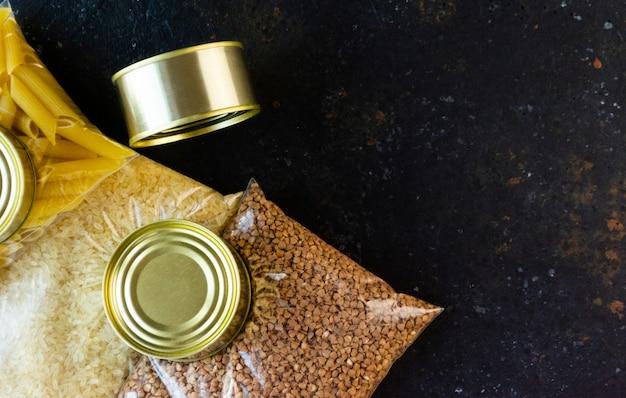 Продовольственный карантин продовольственного кризиса продовольствия изолирован на черном фоне конкретных. рис, гречка, туалетная бумага, консервы. концепция доставки еды, пожертвования, благотворительность. copyspace.