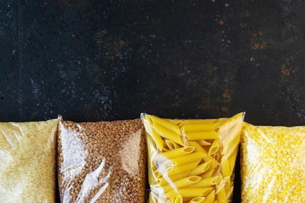 Продовольственный карантин продовольственного кризиса продовольствия изолирован на черном фоне конкретных. рис, макароны, кукурузные хлопья, гречка. концепция доставки еды, пожертвования, благотворительность. copyspace.