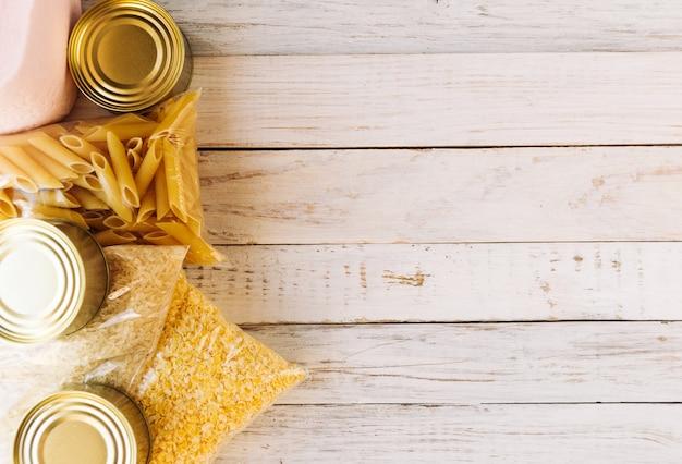 Продовольственный кризис карантина поставок продовольствия, изолированный на белом деревянном фоне. рис, макароны, кукурузные хлопья, туалетная бумага, консервы. концепция доставки еды, пожертвования, благотворительность. copyspace.