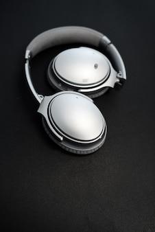 Звук музыки в наушниках. стерео объемное оборудование объекта. наушники на черном фоне и copyspace области для текста. аудио технологии, гаджеты и музыкальная концепция.