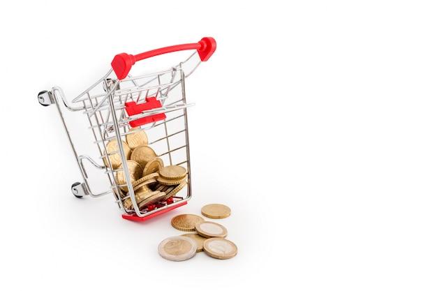 それのユーロ硬貨が付いているショッピングカートは白い背景に落ちています。失敗、貧困、破産の概念図。スーパーマーケットのショッピング、セール、キャッシュバックのテーマ。テキストのcopyspace。