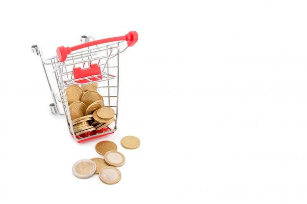 白い背景の上からそれから落ちてくるユーロ硬貨のショッピングカート。失敗、貧困、破産の概念図。スーパーマーケットのショッピング、セール、キャッシュバックのテーマ。テキストのcopyspace。