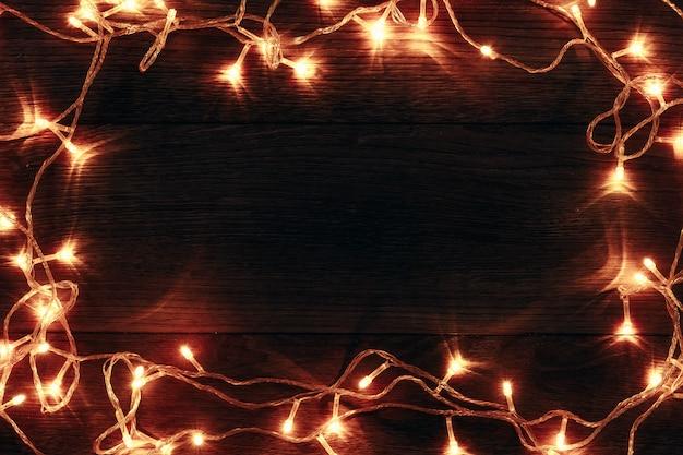 Рамка рождественские гирлянды на деревянном столе. праздники рождество. copyspace. вид сверху.