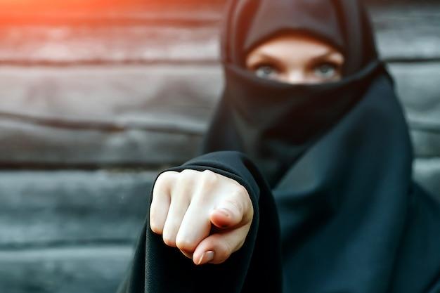 灰色の木に対して顔を閉じた黒いベールの美しい若いイスラム教徒の少女は、カメラに指を向けます。 copyspace。