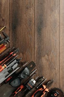Строительный инструмент на коричневый деревянный. вид сверху. картинка, заставка. строительство, ремонт, строительство, производство. copyspace.