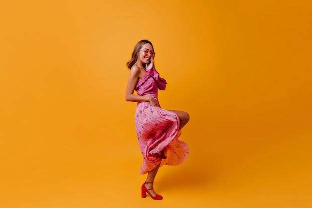 Кокетка в прекрасном нежном розовом платье и красных каблуках с радостью на лице позирует в профиль в теплой одежде.