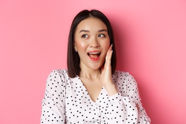 頬を赤らめ、ピンクの背景の上に立って面白がって左を見て赤面しているコケティッシュなアジアの女性