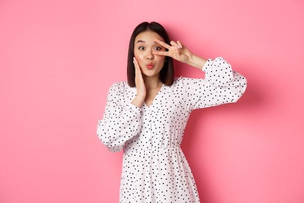 눈에 평화 기호를 보여주는 드레스에 coquettish 아시아 여자, 키스에 대한 주름 입술, 분홍색에 대해 바보 서.