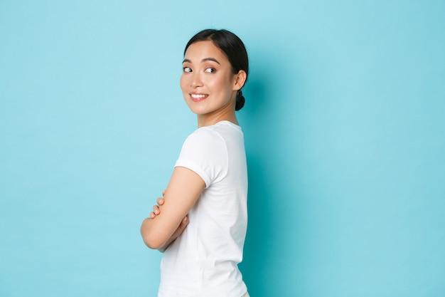 プロファイルに立っている白いtシャツでコケティッシュなかわいいアジアの女の子、興味津々な笑顔で右折し、何か面白いものを見て、良いプロモーションのオファーを見つけ、青い壁に立っています。