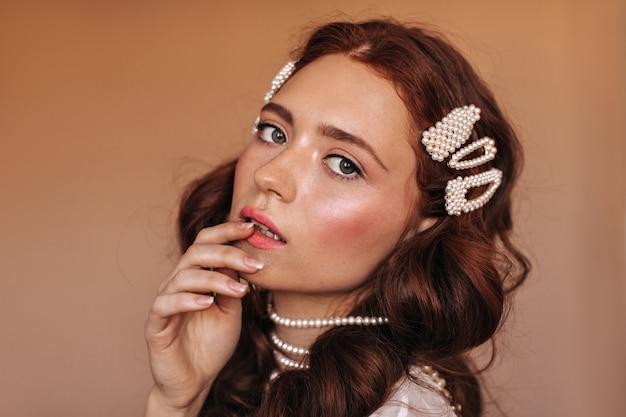 コケティッシュな赤毛の緑色の目の女性は、ふっくらとした唇に優しく触れます。カメラを見ている白い真珠のアクセサリーの女性。